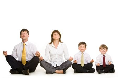 Photo of peaceful family sitting in pose of lotus in a row and meditating over white background photo