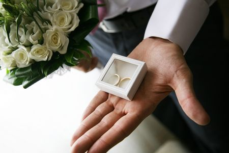 Close-up of small decorative box with two wedding rings in it on human palm photo