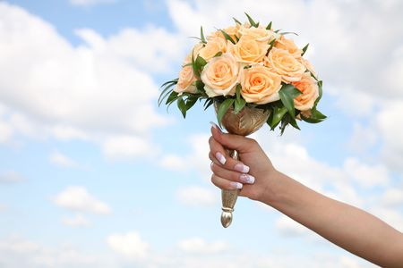 arm bouquet: Close-up of bridal hand holding yellow rose bouquet on background of sky
