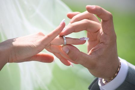 Close-up of groom's hand putting wedding ring on bride's finger Stock Photo - 4646987
