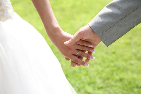 Close-up of bride�s hand holding that of her husband over green background photo