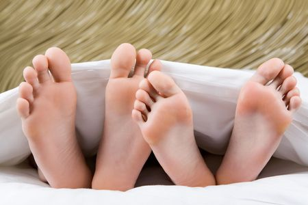 Image of two pairs of bare feet of man and woman lying under blanket