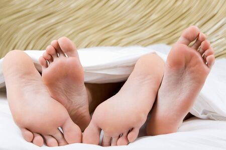 Image of two pairs of bare male and female feet during sleep Stock Photo