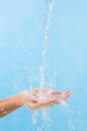 Human palms catching splashing pure water over blue background Stock Photo