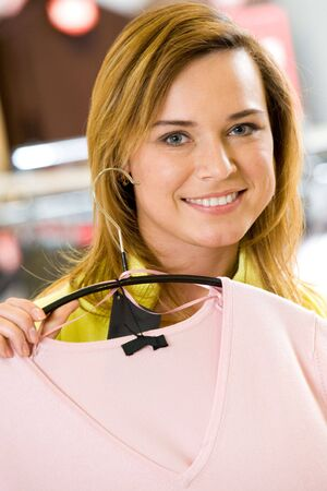 Portrait of pretty woman in the mall holding new tanktop and looking at camera Stock Photo - 4647013