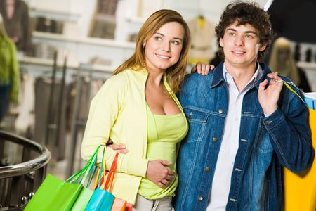 Portrait of loving couple doing shopping and looking at nice clothes in trade center photo