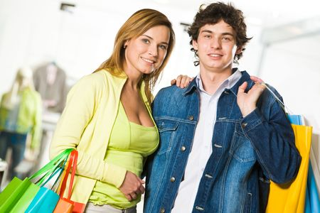 amorous: Portrait of amorous couple looking at camera with smiles after great shopping