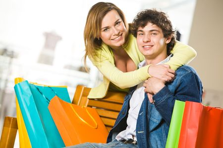 customer relationship: Attractive woman embracing her boyfriend while he sitting on bench in mall