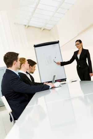 Smart and confident employee pointing at whiteboard while presenting her ideas to business partners photo