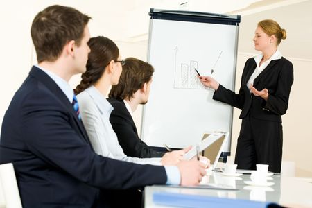 Photo of serious business people listening to female manager pointing at whiteboard while presenting new project Stock Photo - 4681038
