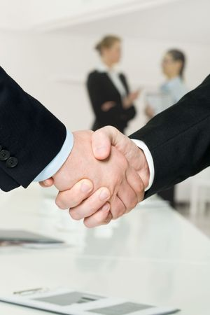 ovation: Photo of handshake of business partners after striking deal on background of communicating women