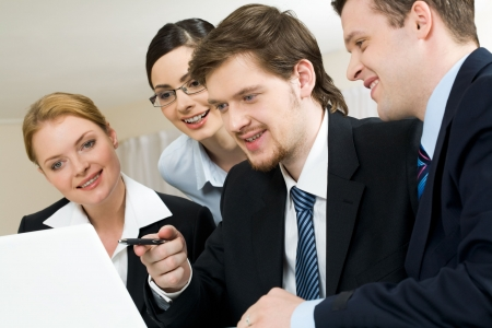 workteam: Portrait of friendly workteam looking at monitor of laptop while confident businessman pointing at screen Stock Photo