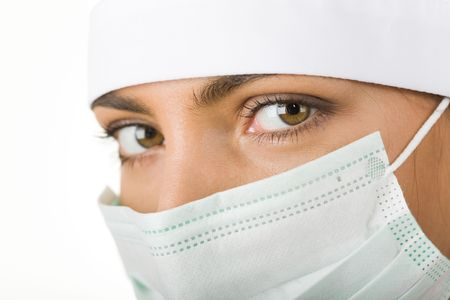 Close-up of pretty assistant wearing mask looking at camera Stock Photo