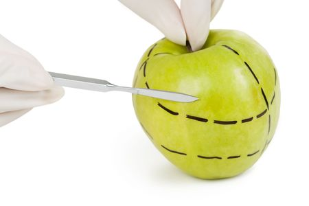 Close-up of green apple with dotted lines and surgical scalpel on its surface photo