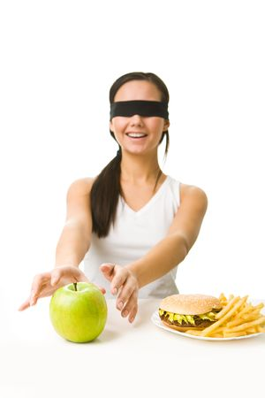 Portrait of young girl with her eyes folded deciding what to eat: an apple or fast food photo