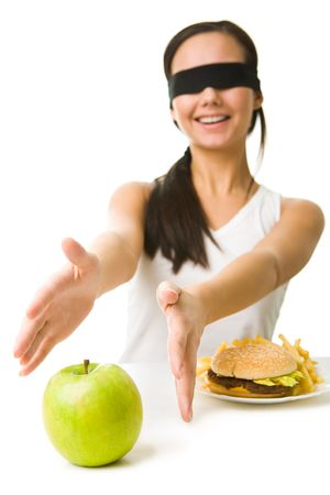 Portrait of young girl with her eyes folded stretching her arms towards green apple photo