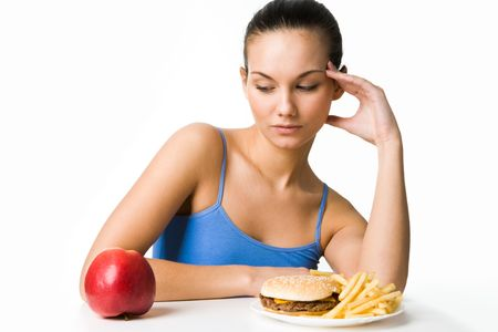 what to eat: Portrait of pretty young girl deciding what to eat: an apple or hamburger with fried potatoes