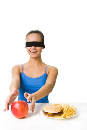 Portrait of young girl in blindfold preferring to eat fresh and ripe apple rather than hamburger or French fries photo