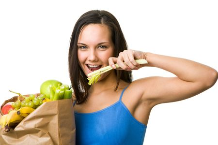 Portrait of pretty girl holding paper sack with fruits and vegetables and eating celery photo