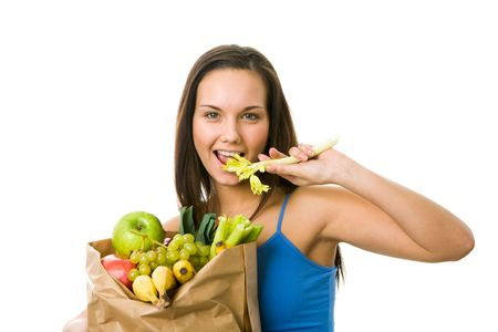 Portrait of pretty girl with paper sackfull of fruits and vegetables while eating celery and looking at camera with smile photo