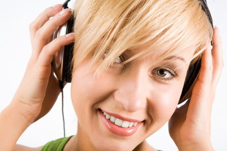 Close-up of pretty teenage girl touching headphones on her head with happy smile photo