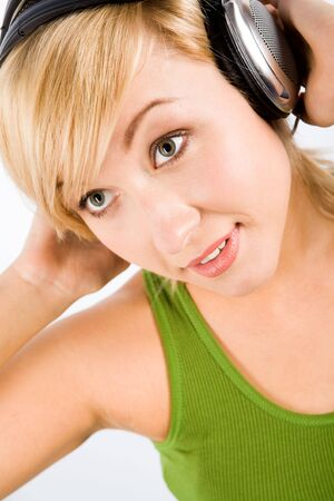 Close-up of pretty teenage girl touching headphones and looking aside with positive expression photo