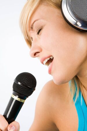 favourite: Image of modern teenage girl with headphones on head singing her favourite song into microphone Stock Photo