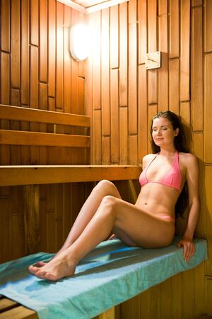 Peaceful woman taking pleasure in hot sauna while sitting on blue towel on wooden bench photo
