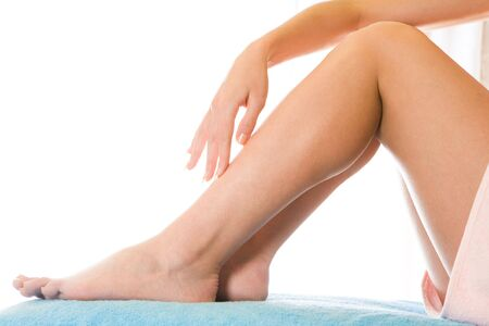 Close-up of soft female legs after depilation over white background photo