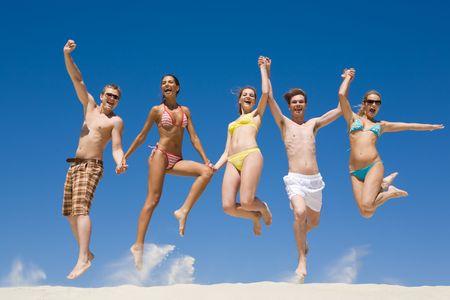 persona saltando: Alegre grupo de amigos para la celebraci�n de las manos unos a otros y saltar