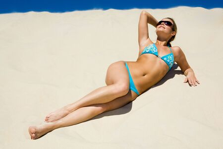 hot girl lying: Photo of pretty woman lying on the sand and sunbathing