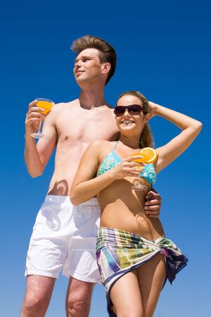 Portrait of relaxing woman in sunglasses and bikini holding cocktail in hand with handsome man standing near by photo