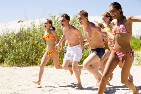 Portrait of joyful teenagers on sandy beach going to run into water photo