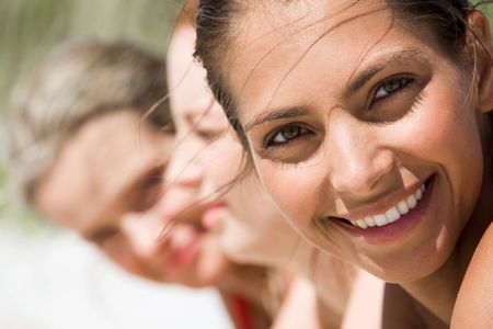 Face of young woman looking at camera on hot summer day with her friends at background photo