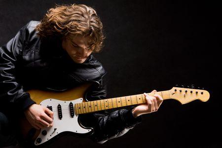 rock hand: Ritratto di giovane chitarrista moderno strumento di gioco su sfondo nero