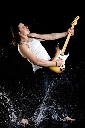 Portrait of young performer playing electrical guitar in water splashes Stock Photo - 4704696