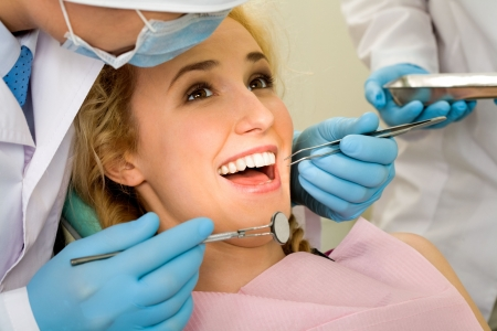 oral surgery: Image of young lady with dentist over her before checking oral cavity
