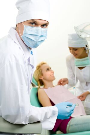 Portrait of confident doctor in sterile mask on background of his assistant helping patient Stock Photo - 4843195