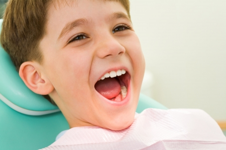 wide open: Photo of youngster with his mouth wide open during checkup at the dentist�s Stock Photo