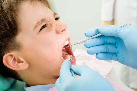Close-up of little boy opening mouth for dental checkup in stomatological office photo