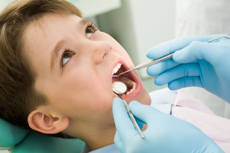 saliva: Close-up of little boy opening his mouth during dental checkup Stock Photo