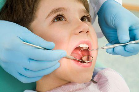 dentiste: Close-up de l'ouverture de son petit garçon de la bouche pendant l'inspection de la cavité buccale