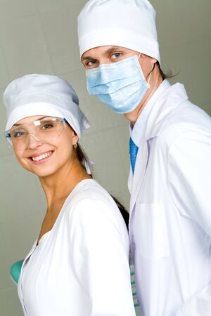 Image of confident doctor with his pretty assistant both looking at camera  Stock Photo - 4843221
