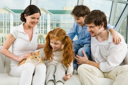Portrait of young man and woman enjoying weekend day with their children and cute cat photo