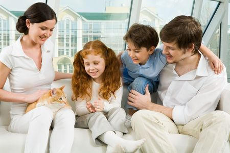 Photo of cheerful children and their father looking at cat on female�s knees during home rest photo