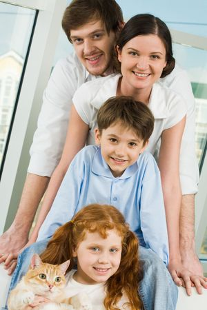 Photo of cheerful children and their parents looking at camera with smiles photo