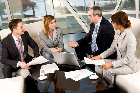 business consulting: Portrait of confident business partners communicating in office at meeting Stock Photo