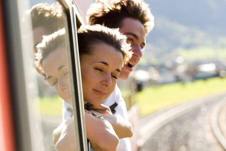 Photo of romantic couple looking out of train window while their travel