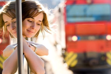 Photo of pretty passenger looking out of train window with wagon near by photo