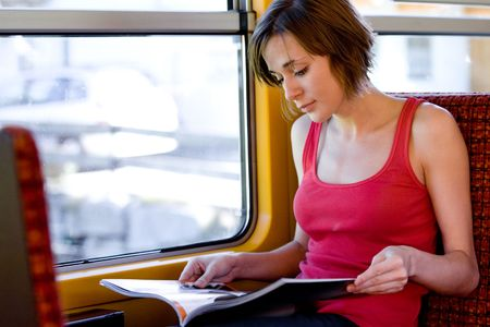 Photo of traveling passenger reading magazine in train by the window photo